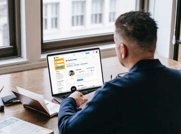 Fotka, kde sedí student u počítače a kouká na seznam učitelů k dispozici na Teacher Creature.